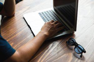 crop unrecognizable man using laptop at table