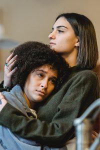 serious young woman embracing sad black girlfriend